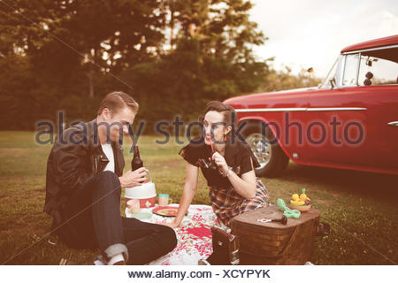 USA, Connecticut, Couple having picnic, vintage car in background - Stock Photo