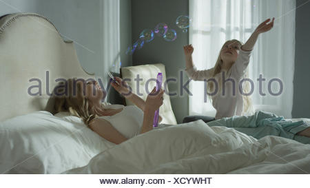 Mother and daughter playing and blowing bubbles in bedroom - Stock Photo