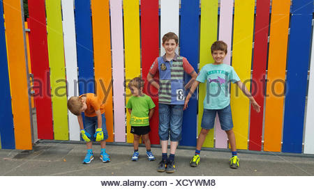 four brothers standing in front of a colorful batten fence - Stock Photo