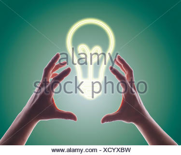 Person's hands reaching for digitally generated image of light bulb - Stock Photo