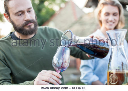 Man pouring red wine on garden party - Stock Photo