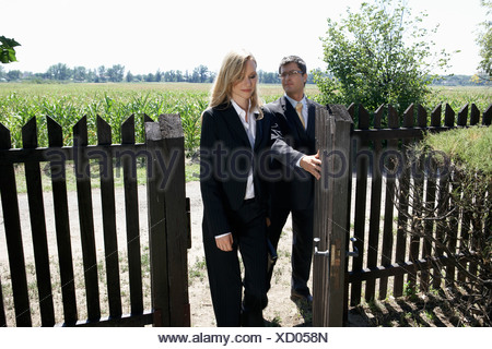 Businessman opening gate for businesswoman. - Stock Photo