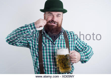 Man holding a beer glass and twirling his moustache - Stock Photo