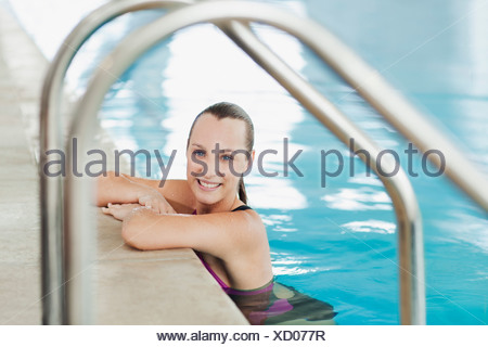 Portrait of smiling woman leaning on edge of swimming pool - Stock Photo