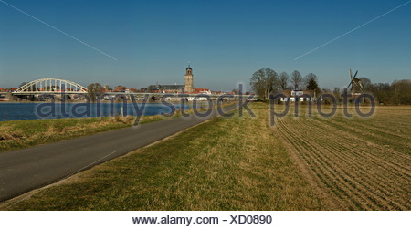 Netherlands Holland Europe Deventer Overijssel landscape field meadow water winter bridge Bolwerks windmill Ijssel bridge - Stock Photo