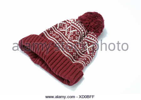 A red and white woollen bobble hat - Stock Photo