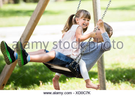 Brother and Sister Enjoying On Swing In The Park - Stock Photo
