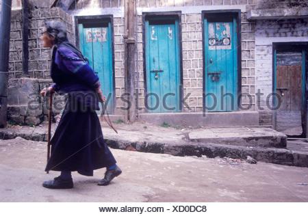 An elderly Tibetan woman walks the streets of McLeod Ganj while holding her prayer beads behind her back.Dharamsala Kangra Vall - Stock Photo