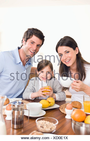 Portrait young family sitting at breakfast table - Stock Photo