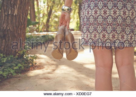 Rear view of a woman holding pair of shoes - Stock Photo