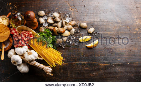 Dark wooden background with Ingredients for cooking Spaghetti vongole - Stock Photo