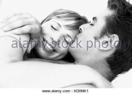 Couple embracing, man kissing woman's forehead, woman's eyes closed - Stock Photo