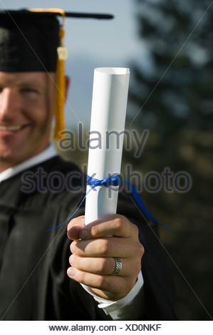 Male graduate holding diploma - Stock Photo