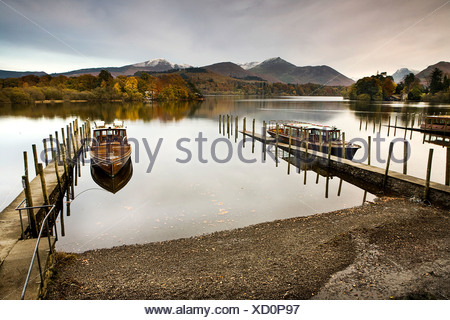 Two small boats moored next to wooden jetty's on a lake with mountain views - Stock Photo