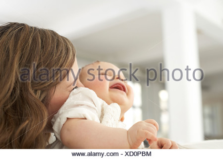 Mother kissing her laughing baby girl - Stock Photo