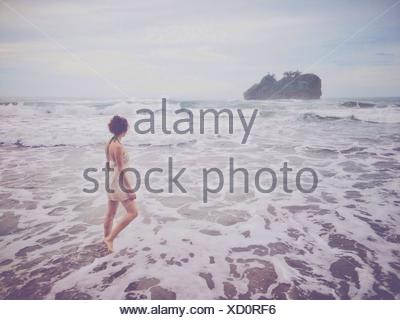 Rear View Of Young Woman Walking In Water At Beach - Stock Photo