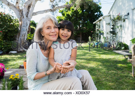 Portrait smiling affectionate grandmother and granddaughter in backyard - Stock Photo
