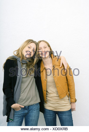 Two young female friends, one with arm around the other's shoulders, both smiling at camera - Stock Photo