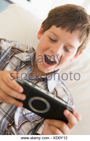 Young boy with handheld game indoors - Stock Photo