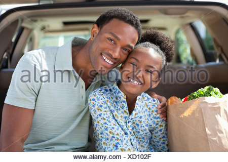 Father and daughter unloading groceries from car - Stock Photo