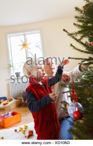 Sweden, Mother with son decorating christmas tree - Stock Photo