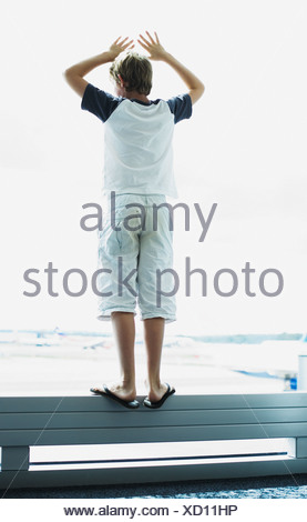 A boy looking out a window at an airport - Stock Photo