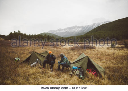 Smiling male hunter friends drinking coffee outside tents at campsite in remote field below mountains - Stock Photo