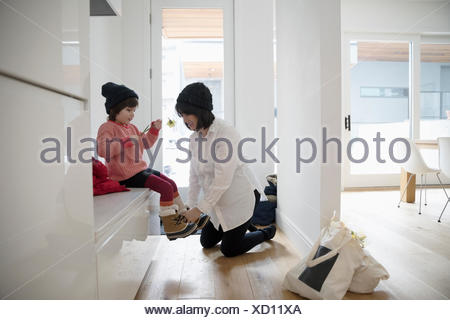 Pregnant mother putting boots on toddler daughter - Stock Photo
