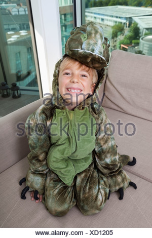 High angle portrait of happy boy in dinosaur costume sitting on sofa at home - Stock Photo