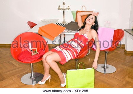 Young woman exhausted after shopping - Stock Photo