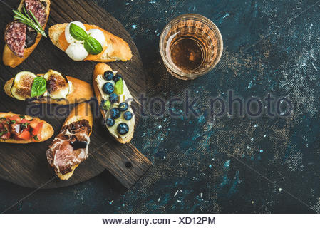 Italian crostini with various toppings on round wooden board and glass of rose wine over black plywood background, top view, cop - Stock Photo