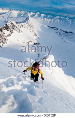 Skier climbs high to ski the steep southwest face of Kickstep Mountain, Turnagain Pass, Kenai Mountains in Southcentral Alaska - Stock Photo