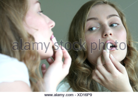 Reflection of young woman applying lipstick in mirror - Stock Photo