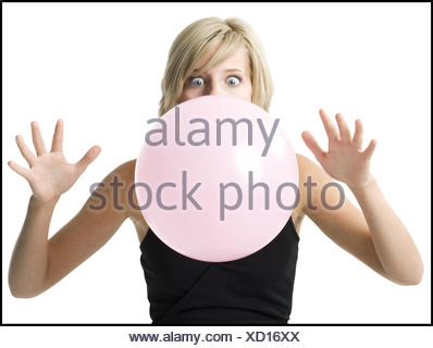 Close up of a young woman blowing bubblegum - Stock Photo