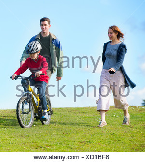 Parents watching son riding bicycle - Stock Photo