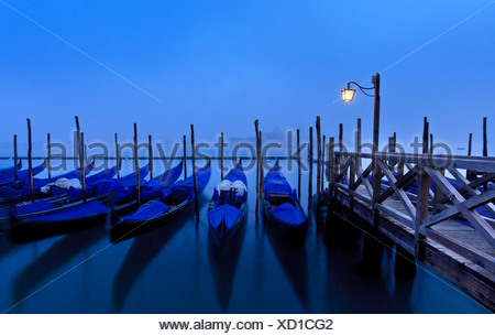 Gondolas tied up at dusk at San Marco with San Giorgio Maggiore in the distance, Venice, Italy, Europe, Europe - Stock Photo