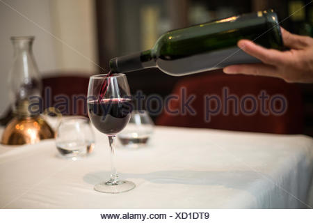 Waiter pouring a glass of red wine - Stock Photo