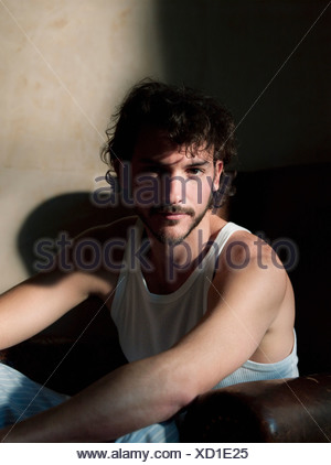 man in old chair looking at camera - Stock Photo
