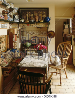 Cat On Antique Windsor Chair In Cluttered Cottage Dining Room With Tapestry  Cushions On Wooden Settle