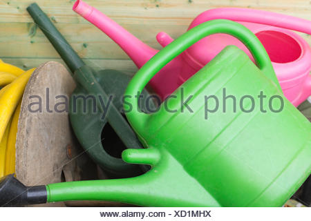 Various watering cans at garden - Stock Photo