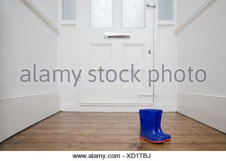 Childrens boots by door - Stock Photo