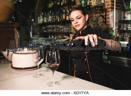 Waitress serving red wine in a bar - Stock Photo