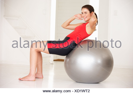 Woman with gym ball in home gym - Stock Photo