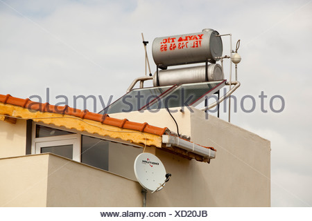 Solar water heating panels on a house roof in Teos, Turkey. - Stock Photo