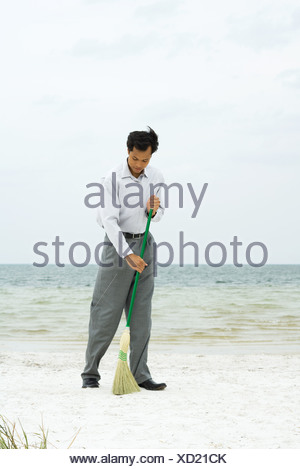 Man standing on beach sweeping with broom, full length - Stock Photo