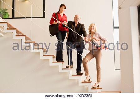 Business people standing on steps - Stock Photo