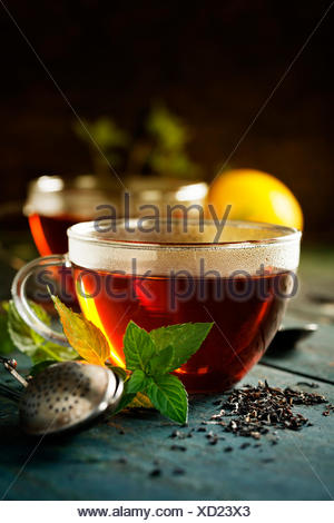 Hot tea cup with mint and sugar on rustic background - Stock Photo