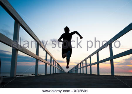 Sweden, Skane, Malmo, Young woman running on pier at sunset - Stock Photo