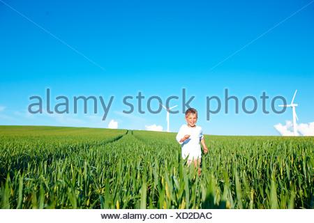 Boy running on field with wind turbines - Stock Photo