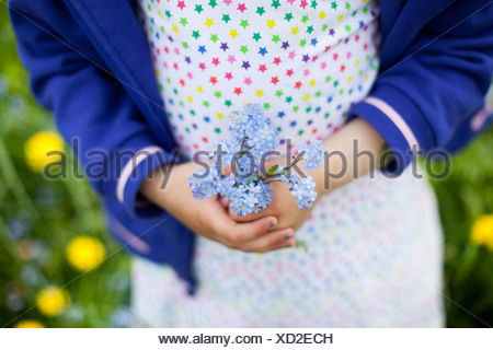 Midsection of little girl (4-5) holding blue flowers - Stock Photo